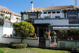 Marbella, spacious corner townhouse near town with  large living room with fireplace and covered porch with access to communal garden and swimming pool